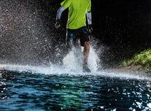 Single runner running, making splash in a stream. Stock Image