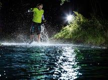 Single runner running, making splash in a stream. Stock Photo