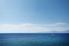 Single Sailboat on Blue. Bright blue sky and water showing the horizon line and a solitary sailboat on the water Royalty Free Stock Photo