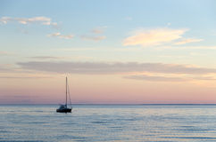 Single sailboat in calm water Royalty Free Stock Images