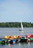 Single sailor on lake, jetty with pedalos. Small sailboat on a lake, jetty with colorful pedalos in foreground stock photo