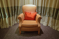 Single seater sofa with classic design. Single seater classic design sofa with small orange pillow and two tones light green curtain in the background stock images
