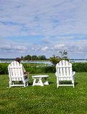 Single senior man in white chairs overlooking bay Stock Images