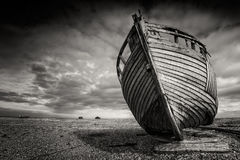 Single shipwrecked boat stranded on pebbled beach. Dungeness, England. Abandoned old fishing boat on a pebble beach in monochrome. Dungeness, England Stock Photos