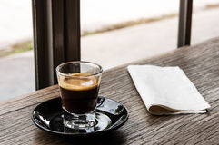 Single shot espresso on wood table. At coffee cafe with warm tone Royalty Free Stock Image