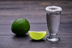 Single shot silver tequila on a black wooden background Stock Images