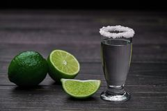 Single shot silver tequila on a black wooden background Royalty Free Stock Photo