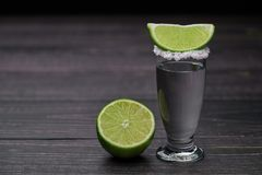 Single shot silver tequila on a black wooden background Stock Photos
