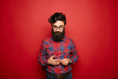 Single shy man with long beard on red. Single shy man with long beard in plaid shirt embarrassed expression over red background Royalty Free Stock Photo