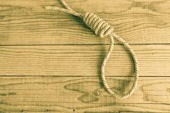 Slipknot on wooden background. Single slipknot on wooden background royalty free stock image