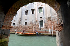 Single small boat framed by doorway, Venice Italy Royalty Free Stock Photos