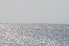 Single Small Boat near Horizon in Infinite Ocean with Silver Reflections on Sunny Day Royalty Free Stock Photography