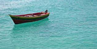 Single small fishing boat in turquoise ocean water Royalty Free Stock Images