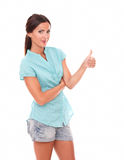 Single smart hispanic lady with thumb up. Gesturing ok sign while standing in white background Royalty Free Stock Photography