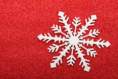 Single snowflake on red background. A single snowflake on red glittery background Stock Images