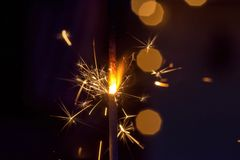 Single sparkler glowing in the night. Macro closeup of a single sparkler glowing and shooting sparks at night Royalty Free Stock Image
