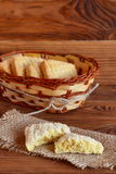 Single square biscuit with sugar on burlap, a bunch of biscuits in wicker basket on brown wooden background Royalty Free Stock Photo