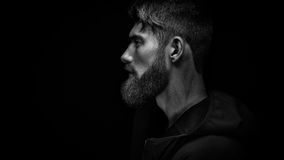 Single standing in profile young handsome serious bearded man in. Black and white image of single standing in profile young handsome serious bearded man in black royalty free stock image
