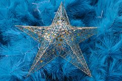 Single star bauble on a blue christmas tree Royalty Free Stock Image