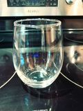 Single Stemless Wine Glass. Sitting on an oven top stock photo