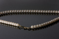 Single strand of vintage pearls reflecting into glass. Pearl necklace with gold clasp on a black background Stock Images
