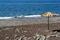 Single straw parasol on black sand beach. Single straw parasol on the Praia Formosa - famous black sand beach on the island Madeira, Portugal stock photography