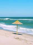 Single straw umbrella on the beach Royalty Free Stock Image