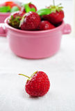 Single strawberry in front of cup with more fruit. Single strawberry on white table, cup with more fruit on the background Stock Images