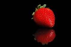 Single strawberry with reflection on black Royalty Free Stock Photo