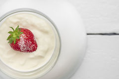 Single strawberry with sugar, cream or yogurt Stock Images