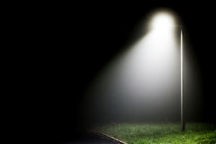 Single street light in the darkness. Single street light illuminating the darkness on a rural road side Stock Photo