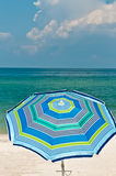 Single stripped, colorful beach umbrella. Standing in a sandy, tropical beach on the Gulf of Mexico Royalty Free Stock Photography