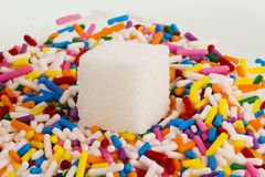 Single sugar cube on decorative sprinkles Royalty Free Stock Images