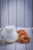 Single sweet bun and pitcher with milk on white Royalty Free Stock Photo