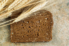 Single of Sweet Dark Whole Grain Bread with Dried Wheat Stalks Stock Photo
