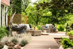 Free Single Swing And Garden Furniture Set On A Wooden Terrace In A G Stock Image - 120974961