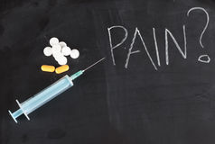 Single syringe and pills on chalkboard with pain. Syringe and pills on chalkboard with pain Royalty Free Stock Image