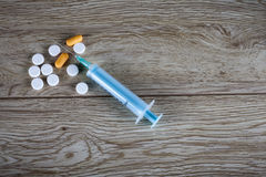 Single syringe and pills on wooden board Royalty Free Stock Photography