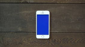 Single Tap Hand Smartphone with Blue Screen. Man Hand Using Vertical Smartphone with Blue Screen Single Tap on the Background of Wooden Table stock footage