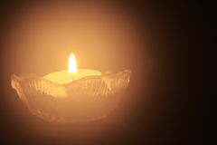 Single tea light candle in the dark. One tealight with a tiny flame against black background Royalty Free Stock Image
