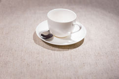 Single teacup and saucer with spoon over gray Royalty Free Stock Photo