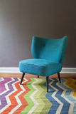 Single teal blue armchair and colorful chevron pattern rug inter Stock Image
