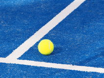 Single Tennis ball on a blue artificial grass court Royalty Free Stock Images