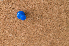 Single Thumb Tack on Cork Board. A single blue thumb tack on a cork board royalty free stock photography