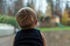 Single toddler child staring out of a window. In evening light into the garden Royalty Free Stock Photography