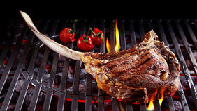 Single tomahawk rib steak on hot grill Stock Image