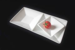 Single tomato on squared dishes Royalty Free Stock Photo