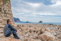 Tourist on the rocky coast in Montenegro. Single tourist sitting on the rocky coast in Montenegro and admiring the beautiful landscape royalty free stock image