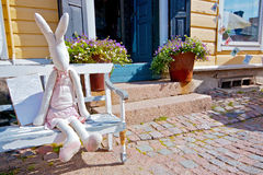Single toy hare sitting on a bench in a village house. Royalty Free Stock Photos