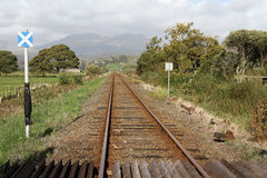 Single track rail-line. Single track rail-line with crossing and sign in a rural setting with trees, fields and mountains Stock Photo